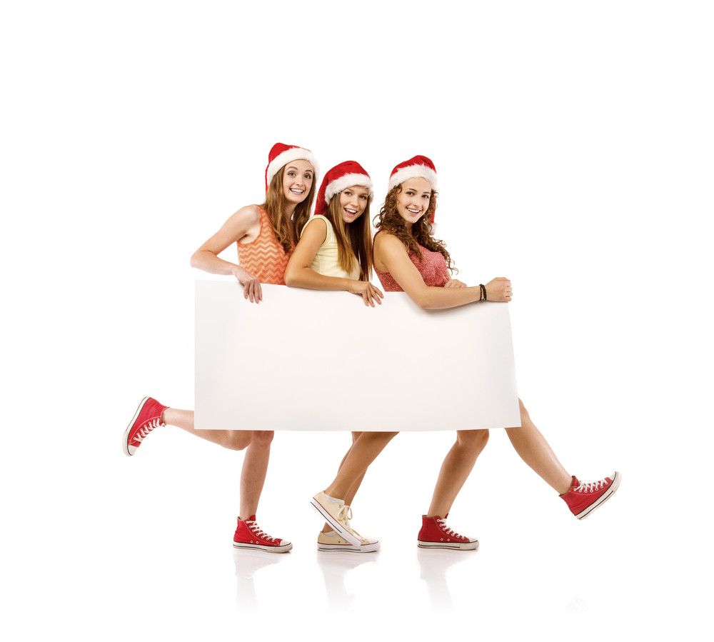 Three young women in santa hats with copy space, isolated on white background