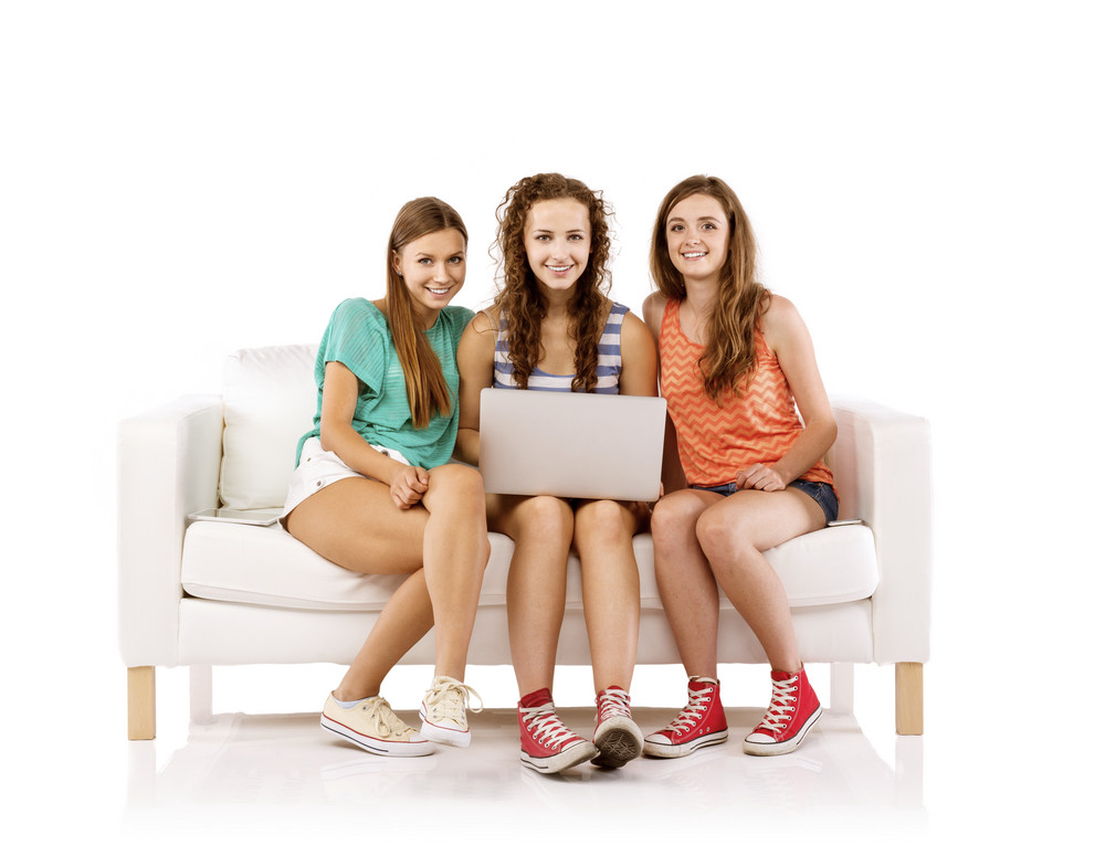 Three young women sitting on sofa and using laptop, isolated on white background. Best friends