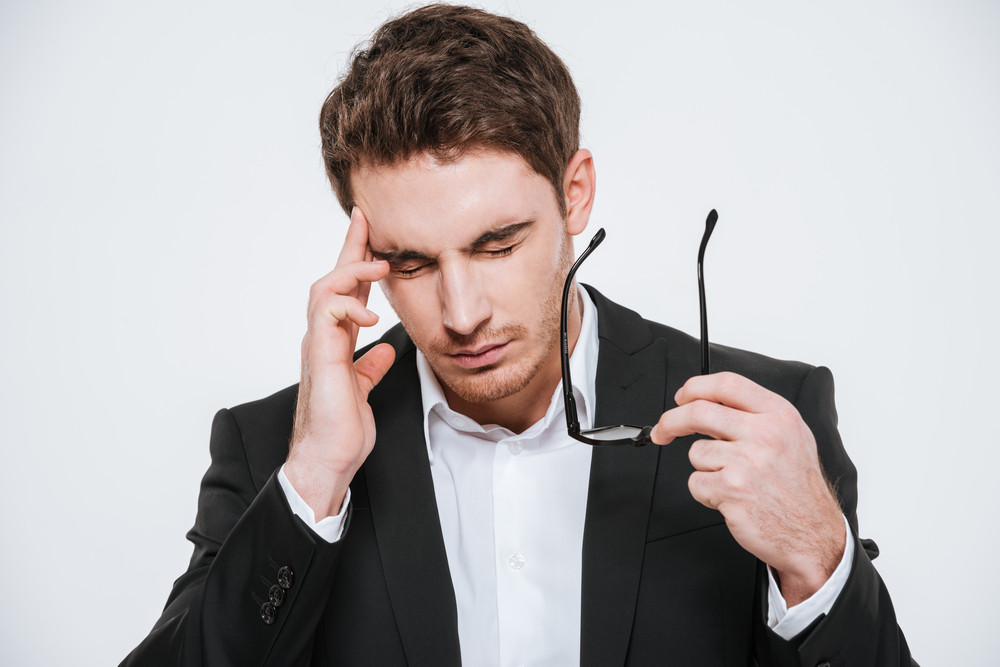 Tired business man rubbing his finger on his temple because of a headache isolated on the white background