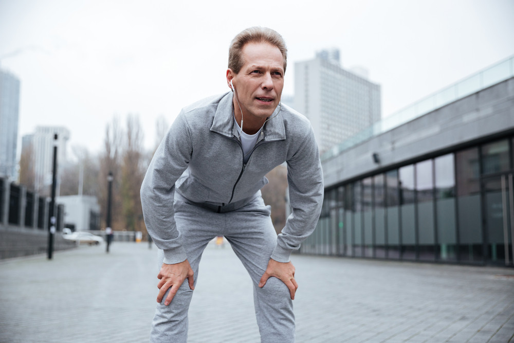 Tired Elderly runner in gray sportswear standing on the street. Front view