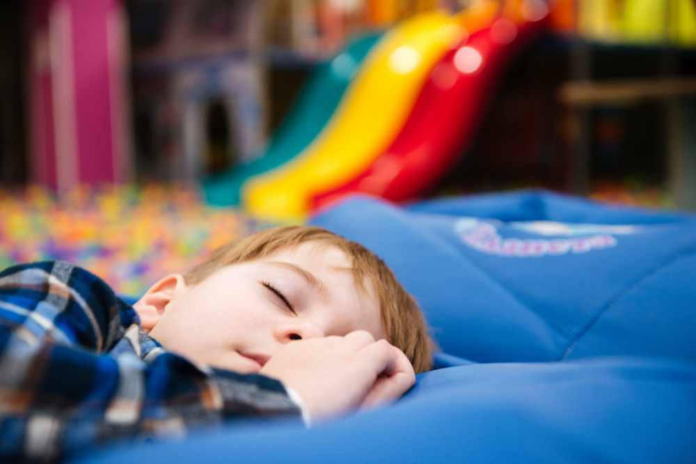 Tired exhausted little boy lying and sleeping at indoor amusement park