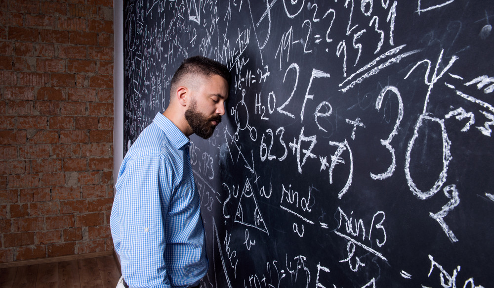 Tired hipster teacher standing and sleeping against big blackboard with mathematical symbols and formulas. Studio shot on black background.