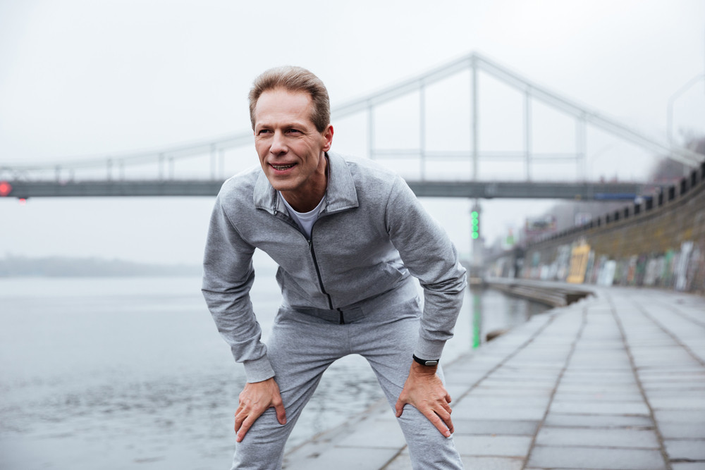 Tired runner in gray sportswear standing near the water