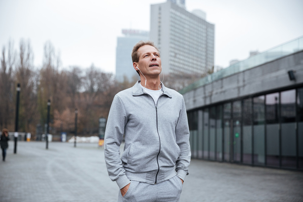 Tired runner in gray sportswear standing on the street with arms in pockets