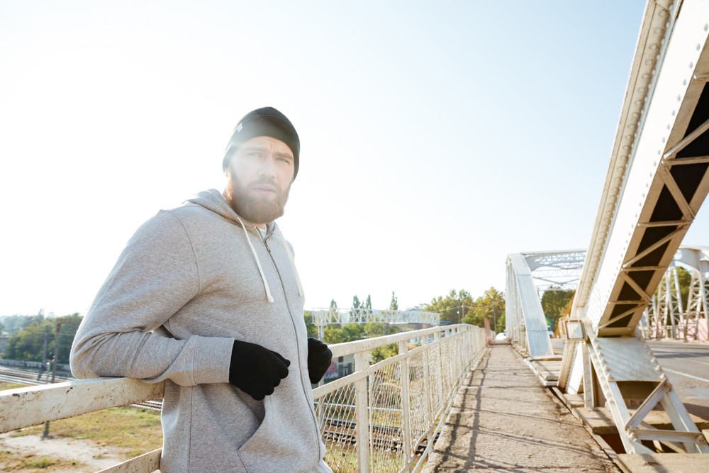 Tired young man athlete in hat resting after workout outdoors