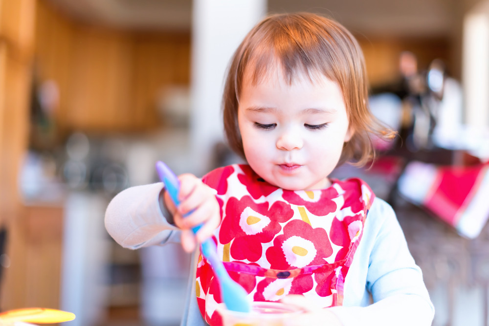 Toddler girl eating food with her spoon in her house