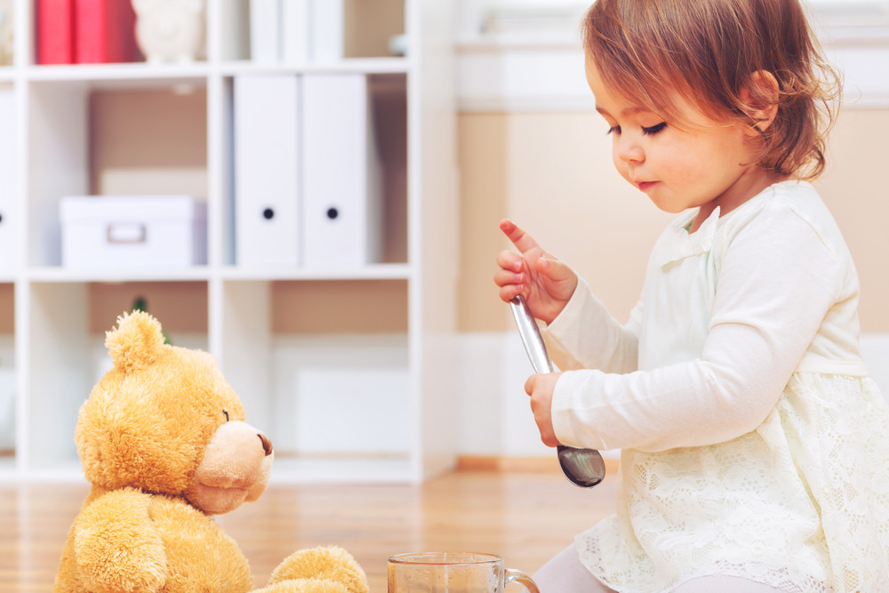 Toddler girl playing with her teddy bear in her house