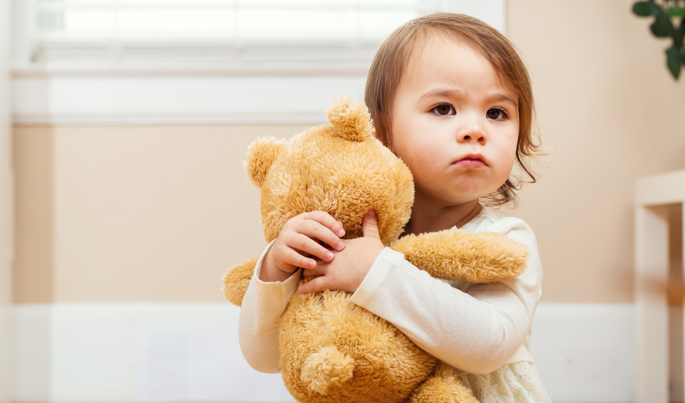 Toddler girl tightly holding her teddy bear in her arms