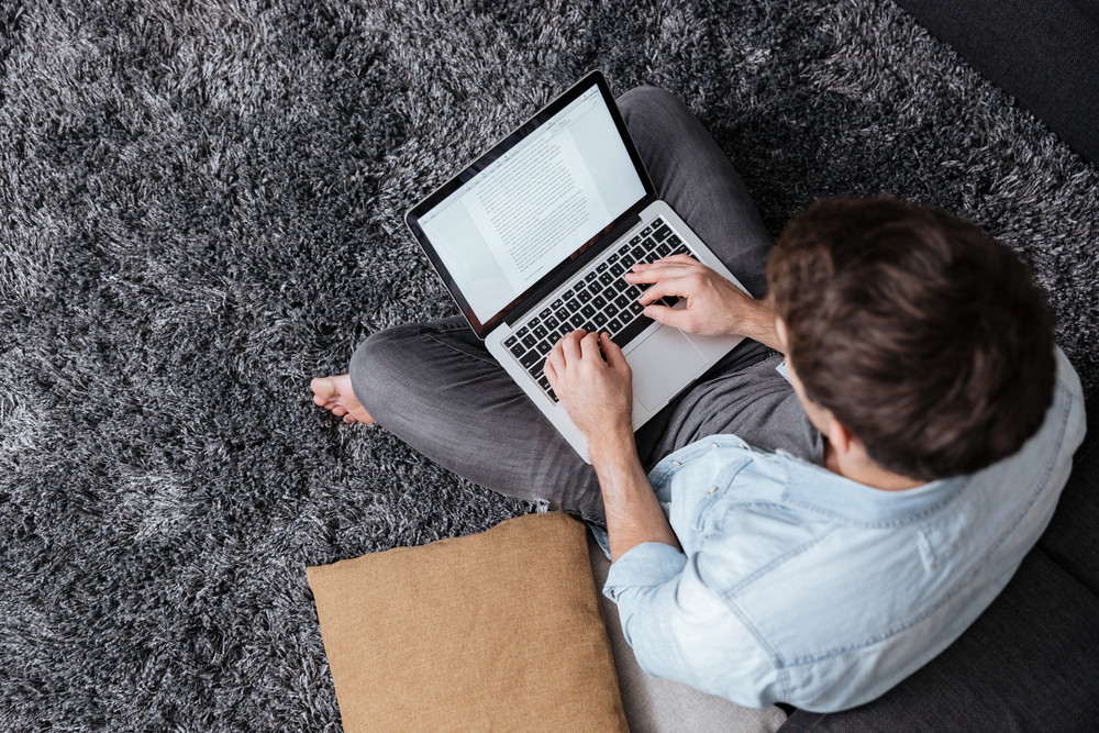 Top view of a casual young man sitting on carpet and typing on laptop computer at home