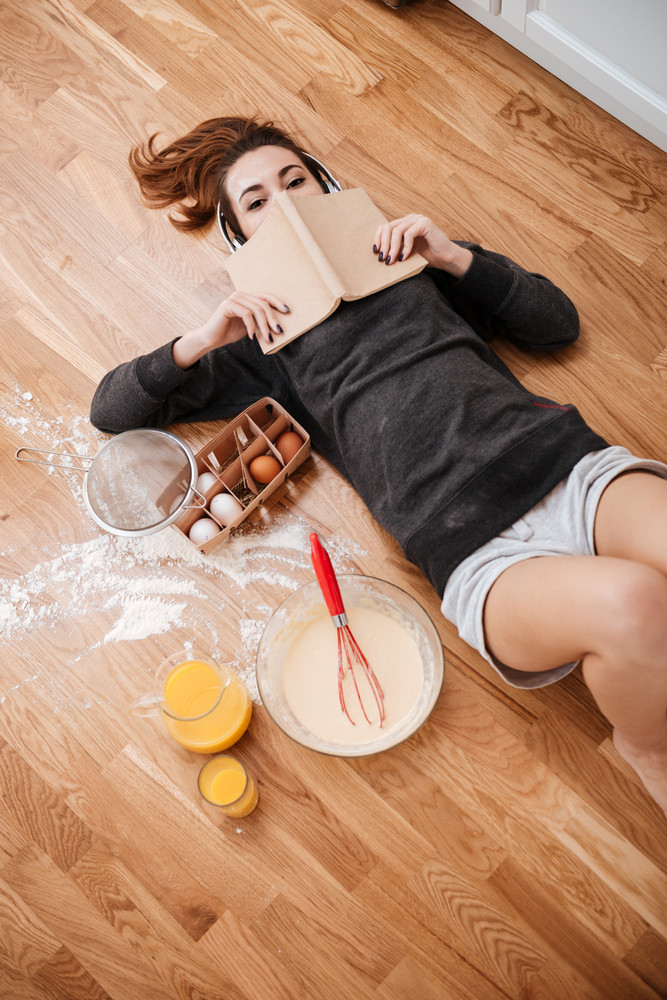 Top view of a cheerful young girl in headphones laying on a kitchen floor and covering face with book