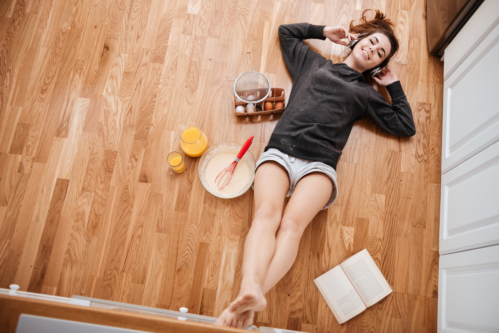 Top view of a happy smiling girl in headphones listening music and cooking breakfast while laying on the kitchen floor