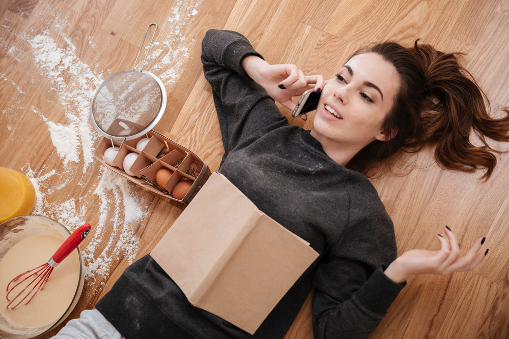 Top view of a young cute girl talking on mobile phone and cooking breakfast while laying on the floor