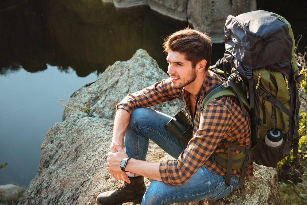 Top view of adventure man sitting on rock looking away.