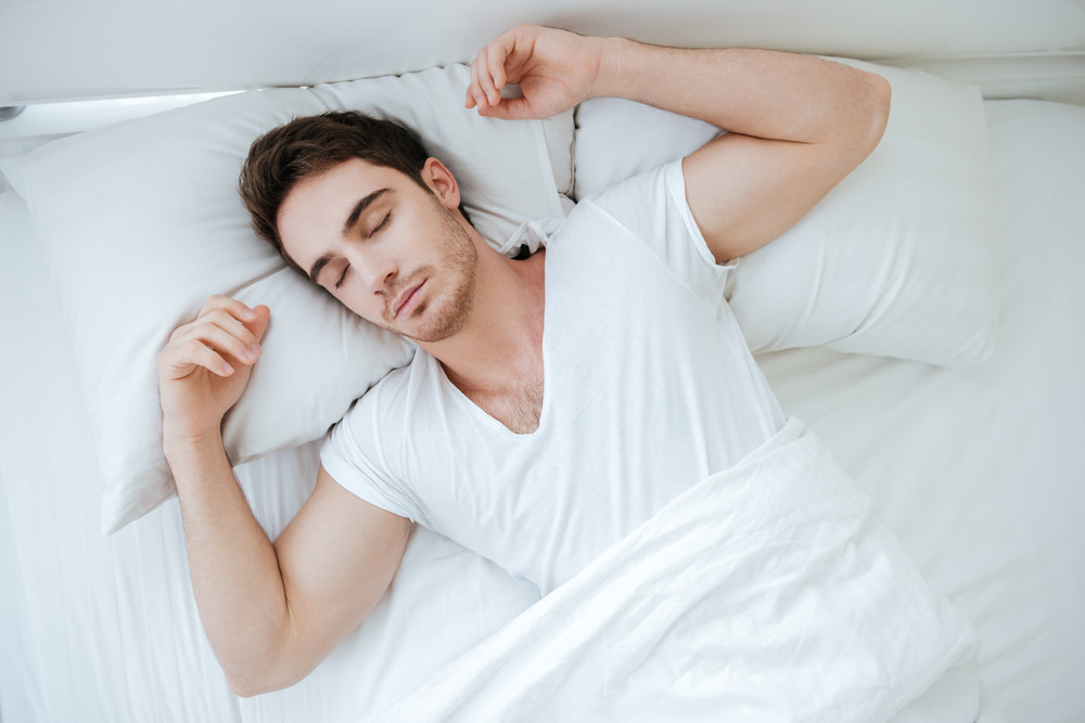 Top view of attractive young man lying and sleeping in bed