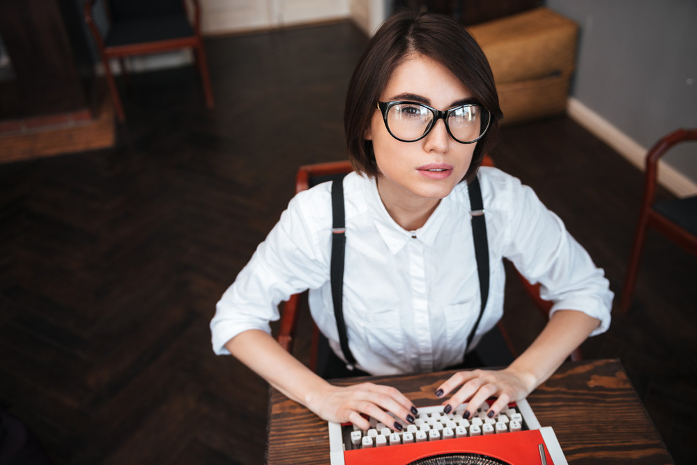 Top view of Authoress in glasses and white shirt sitting by the table, using typewriting and looking at camera