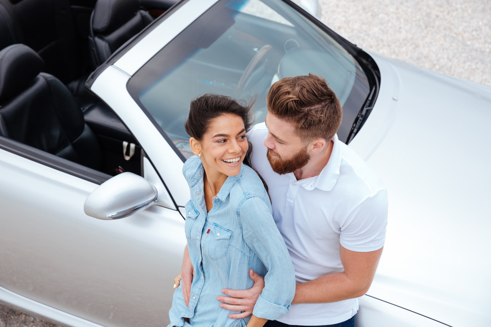 Top view of beautiful young couple embracing while standing near car at the seaside