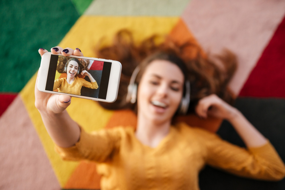 Top view of beautiful young woman in headphones making selfie while lying on carpet at home, focus on phone