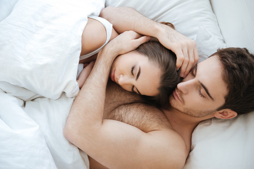 Top view of couple sleeping in bed together