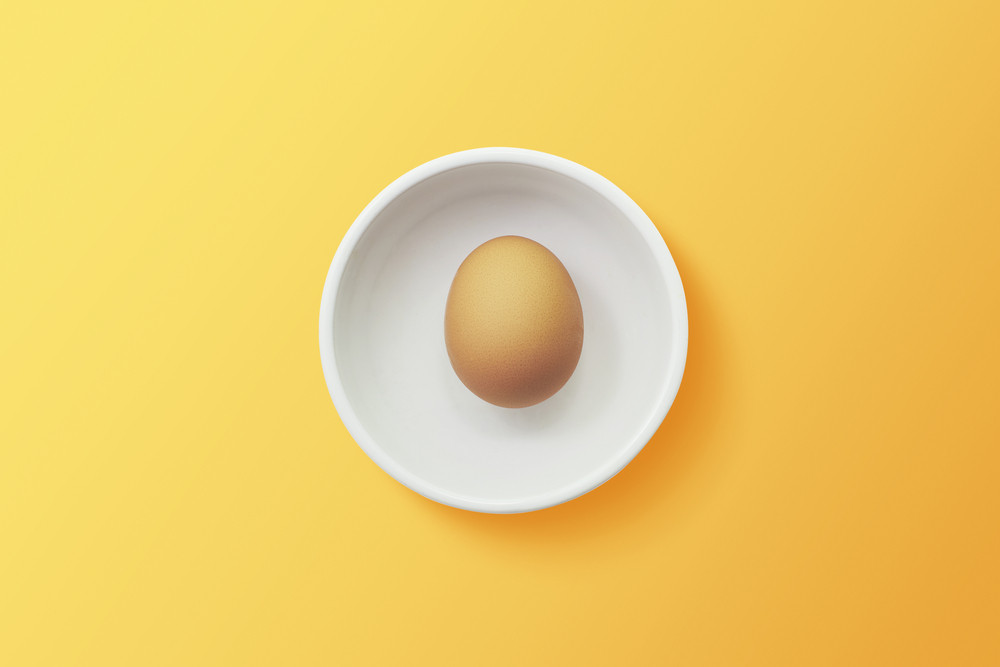 top view of egg in bowl ,orange background