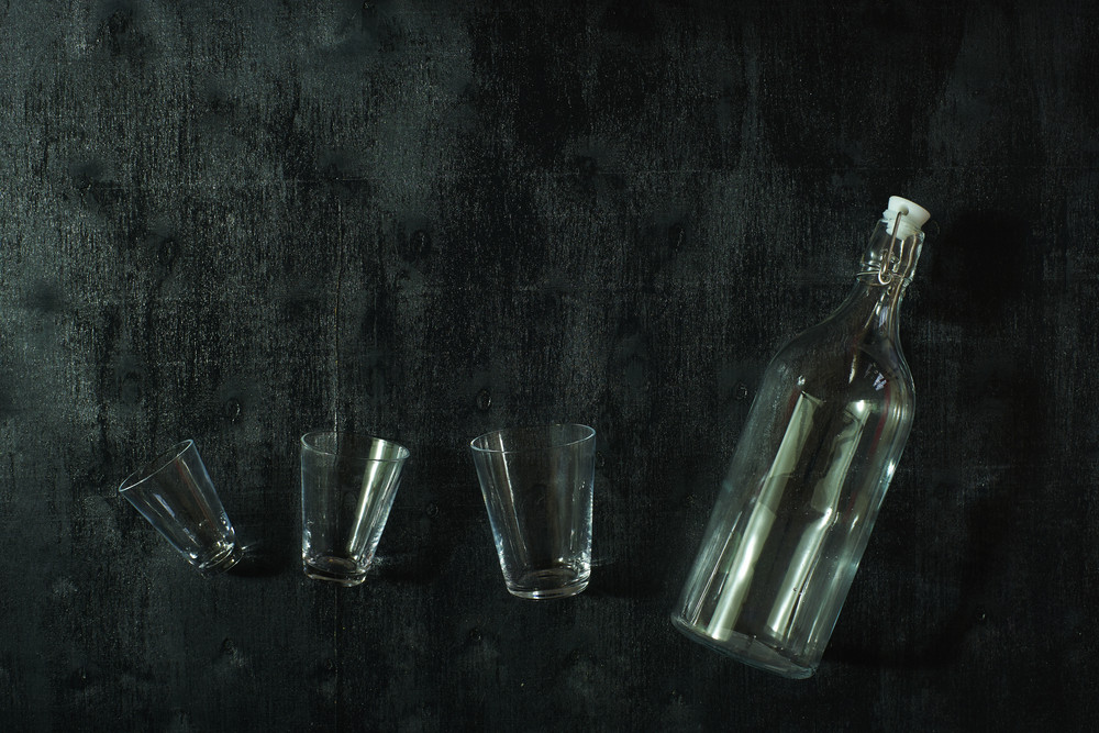 top view of glass of water with a bottle  on wooden table