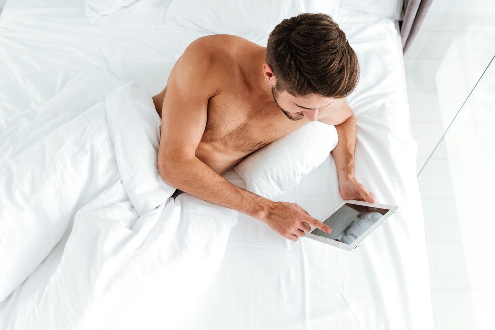 Top view of handsome young man lying in bed and using tablet