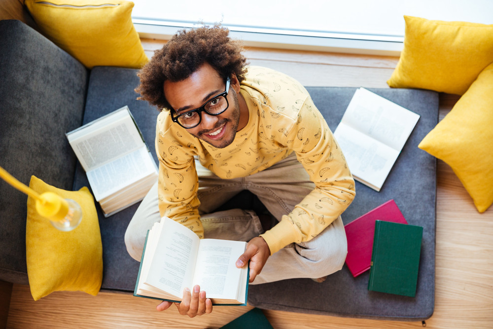 Top view of happy african american young man sitting and studying at home
