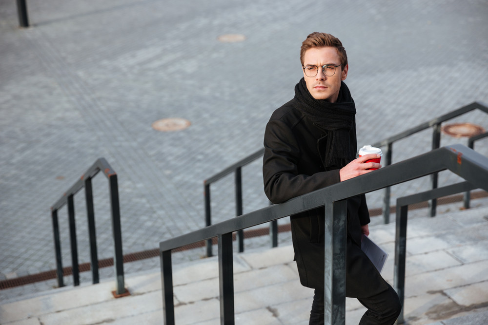 Top view of serious business man in glasses and warm clothes holding coffee and standing on the stairs