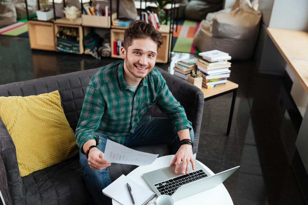 Top view of smiling man in green shirt sitting on sofa with documents and looking at camera. Coworking
