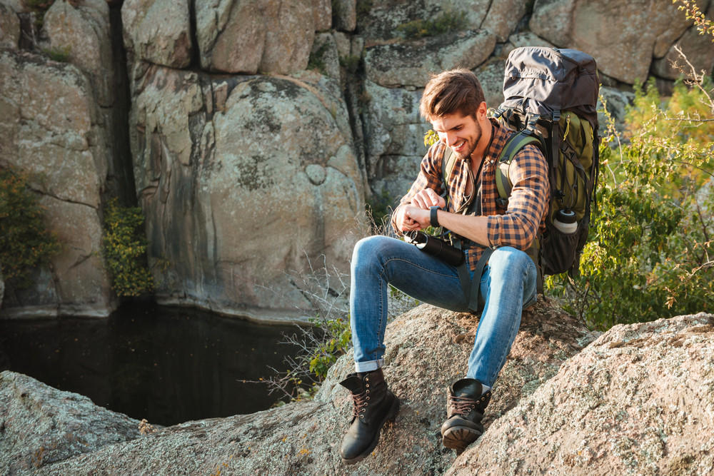 Tourist man sitting on rock looking at wristwatch. near the canyon