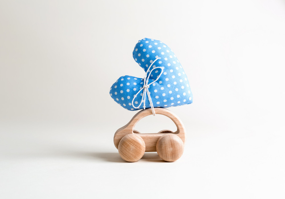 Toy car carrying a heart on an off white background