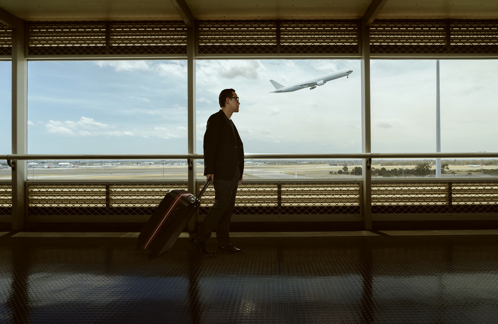 traveling  man and luggage walking in airport terminal and air plane flying outside