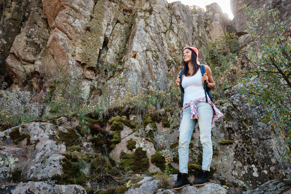Traveling woman with backpacks on rock. full length image