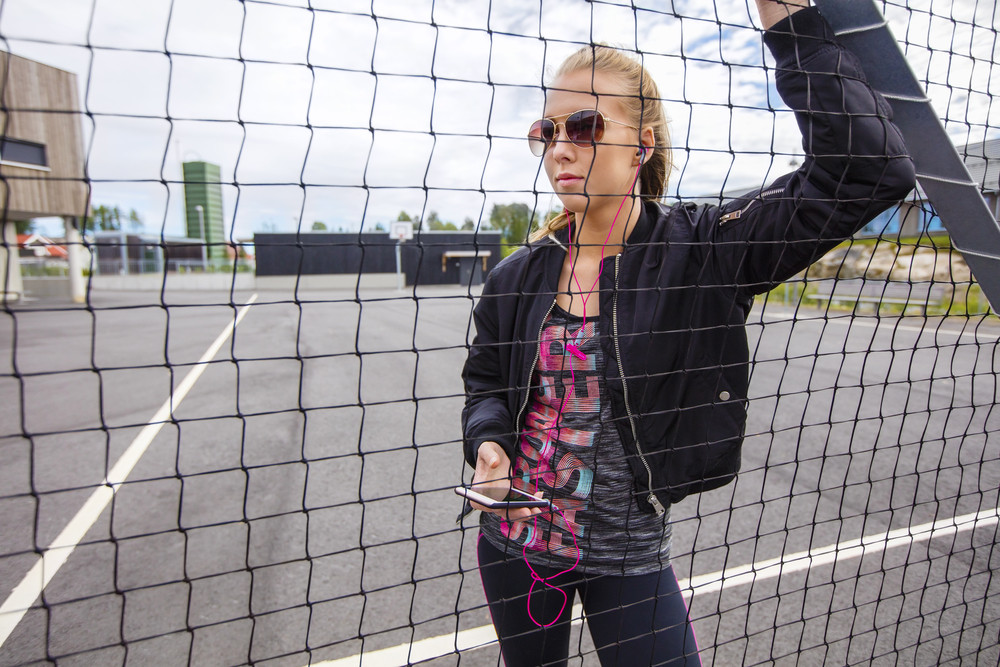 Trendy Woman In Sportswear Listening To Music By Fence