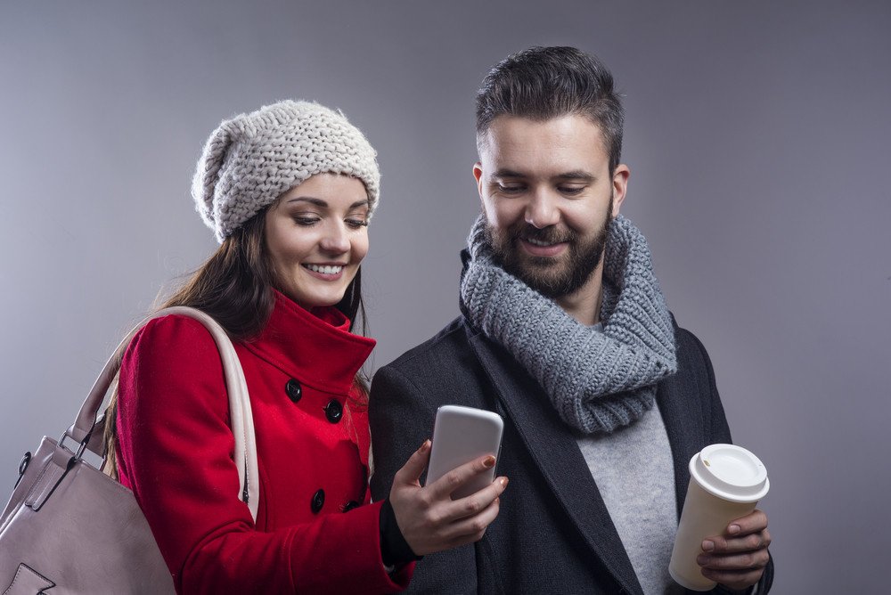 Trendy young hipster couple with coffee and smart phone. Studio shot on gray background.