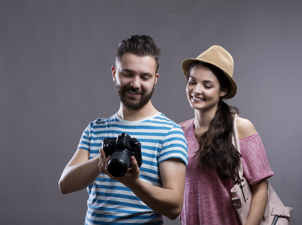 Trendy young hipster tourist couple with camera. Studio shot on gray background.