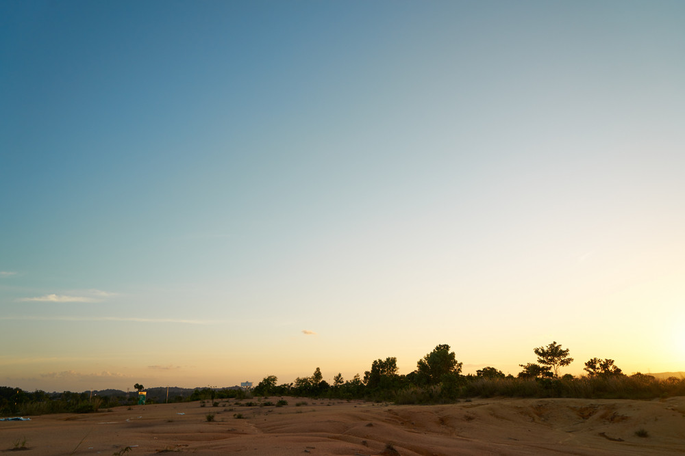 Tropical laterite soil or red earth background. Red mars seamless sand background.with blue sky.