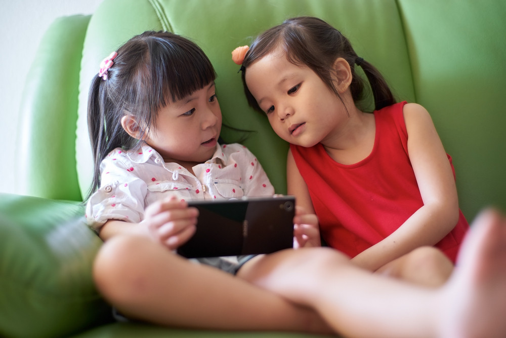 Two Asian girls playing with smart phone