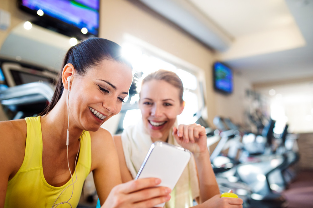 Two attractive fit women in a gym during a break with smart phone