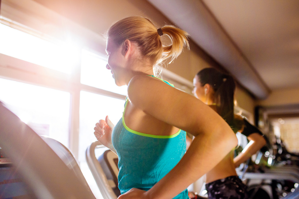 Two attractive fit women running in sports clothes on treadmills in modern gym, sunny day, back view, rear viewpoint