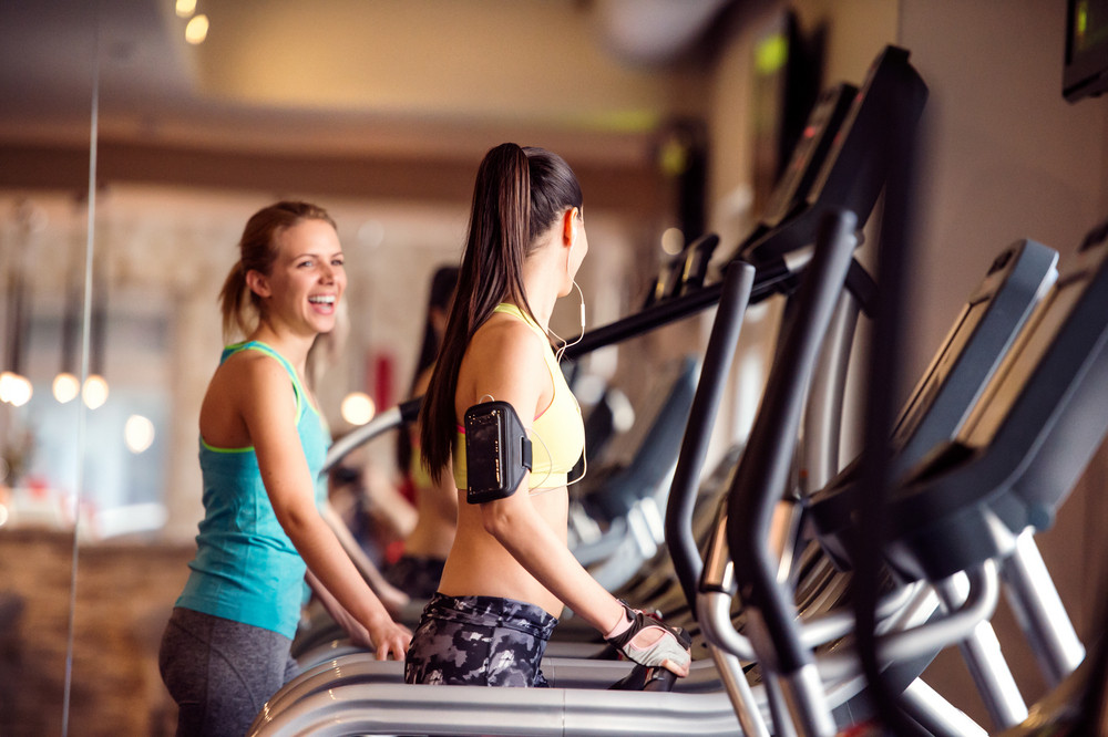 Two attractive fit women running in sports clothes on treadmills in modern gym