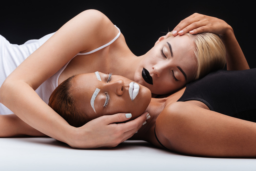 Two attractive young women with creative makeup lying and hugging over black and white background