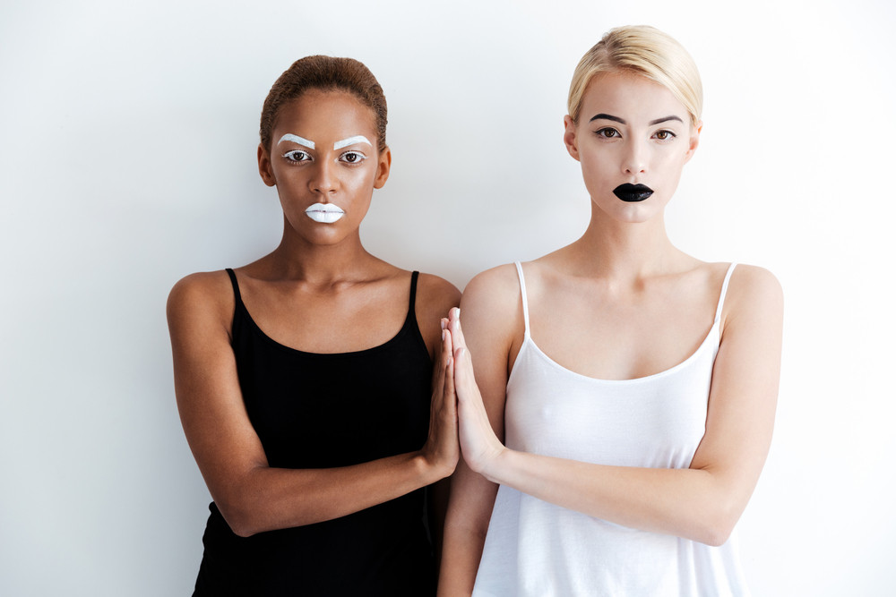 Two attractive young women with fashion makeup standing with hand to hand over white background