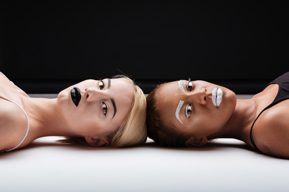 Two attractive young women with stylish makeup lying on white floor over black background
