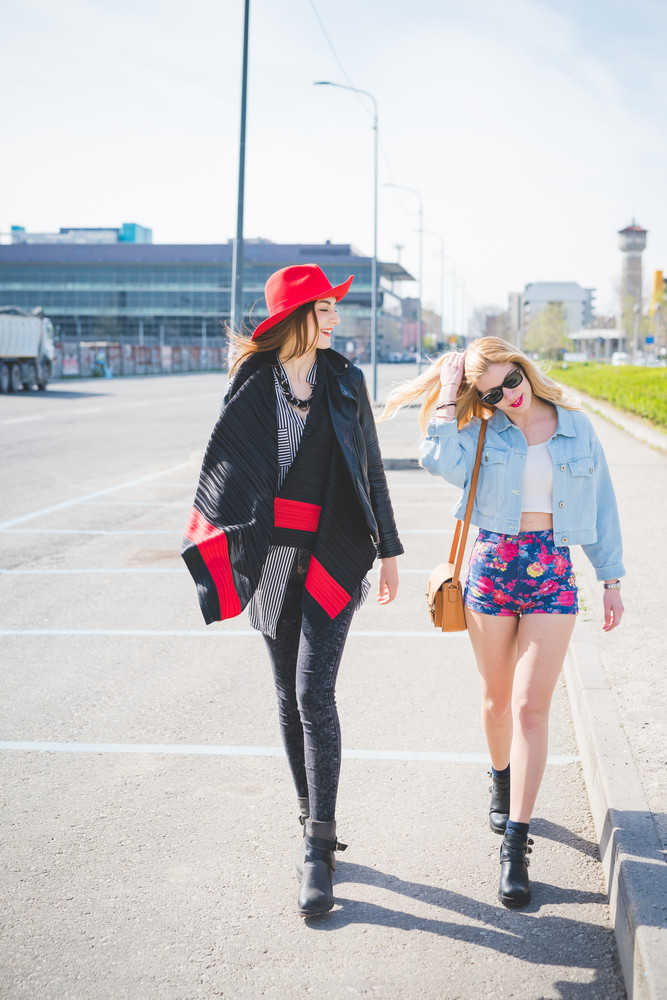 Two beautiful blonde and brunette friends walking through the city having fun - friendship, emancipation concept