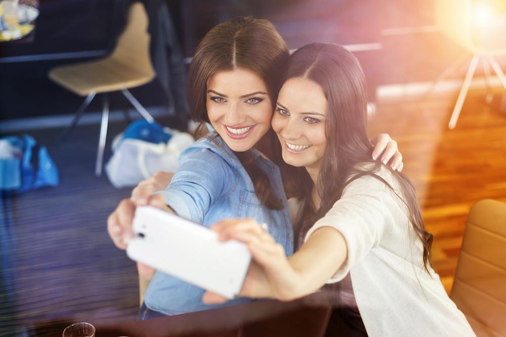 Two beautiful women taking selfie in cafe