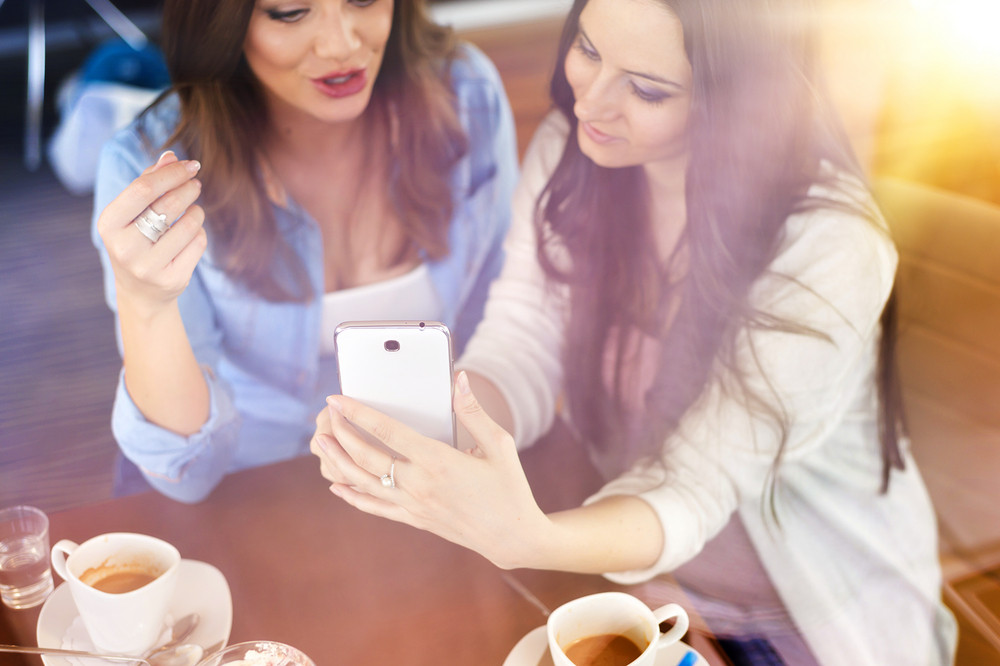 Two beautiful women with smart phone in cafe