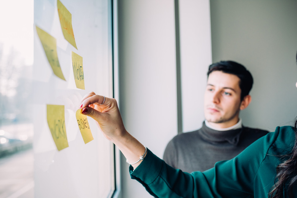 Two business people having a meeting in office. They are standing in front of glass wall with post it notes, pointing and discussing - business, teamwork, brainstorming concept