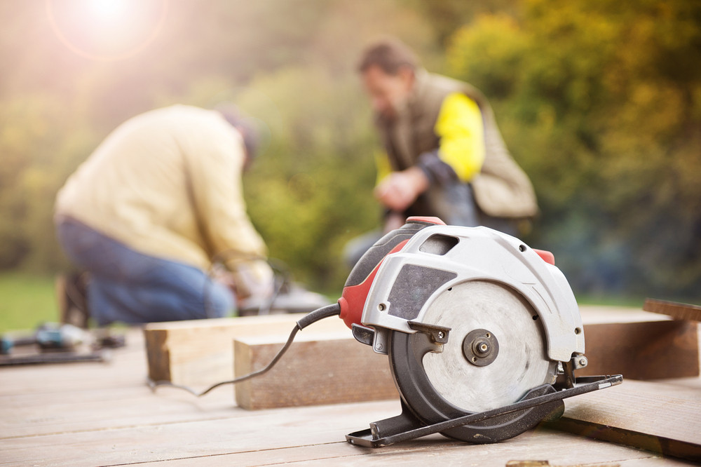 Two carpenters grinding wooden planks outside in terrace