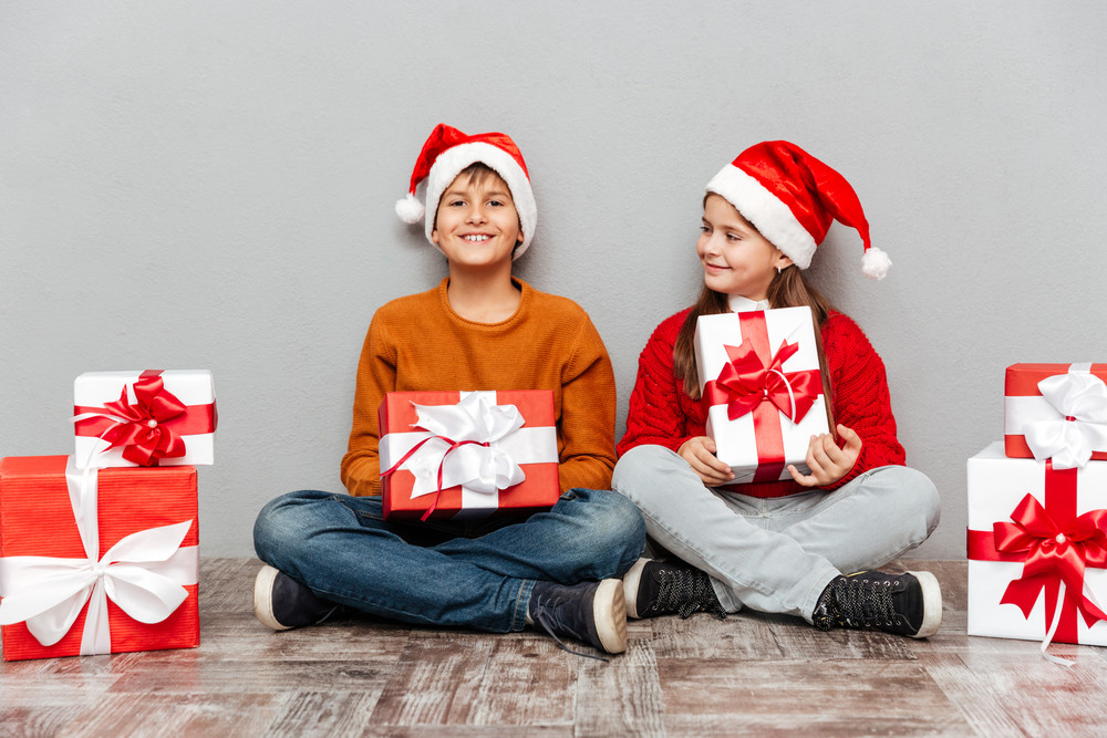 Two cheerful children in santa claus hats sitting and holding present boxes