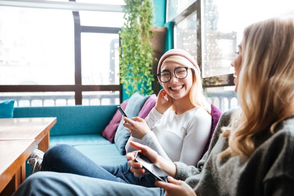 Two cheerful lovely young women using cell phones and laughing in cafe